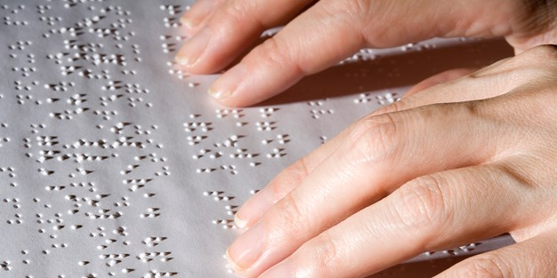 Hands reading braille on a paper. Photo