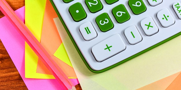 A calculator, a pen and colorful paper. Photo