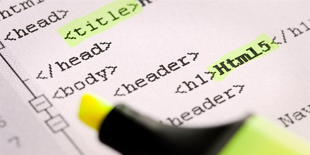 Close-up of html-code printed on paper with highlighter marking words. Photograph