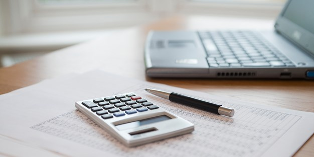 A computer, a calculator and papers on a desk. Photograph