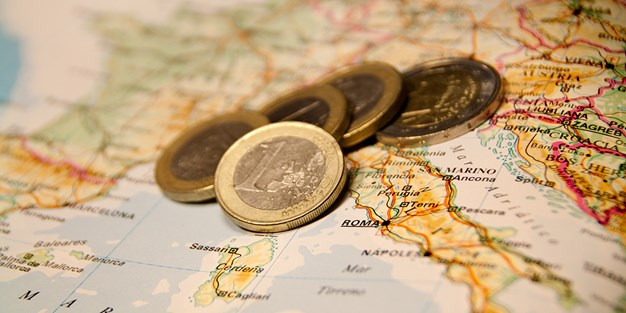 Euros on top of a map of Europe. Photo