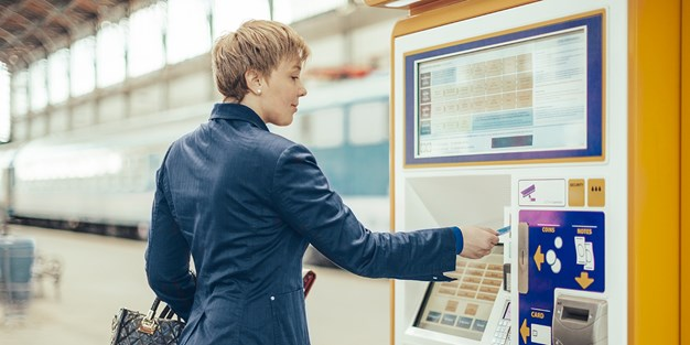 A person buying ticket from a machine. Photo