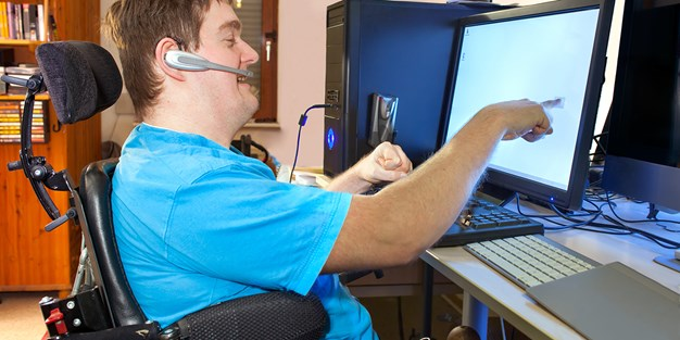 Person in wheelchair at work in front of a computer. Photo