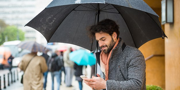 A person walking on a rainy street with an umberella and a smartphone in their hands. Photo