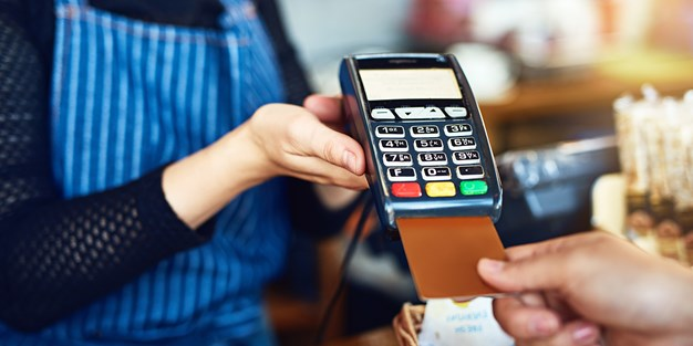 A person pays with a debit card. Photo