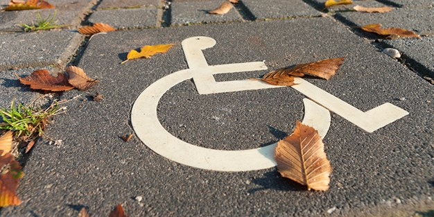 A parking space for persons with disabilities with a wheelchair symbol painted on the ground. Photo
