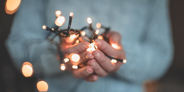 A person holding Christmas lights. Photo.