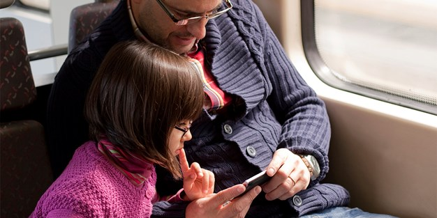 A father and his daughter looking at the screen of a smartphone. Photo