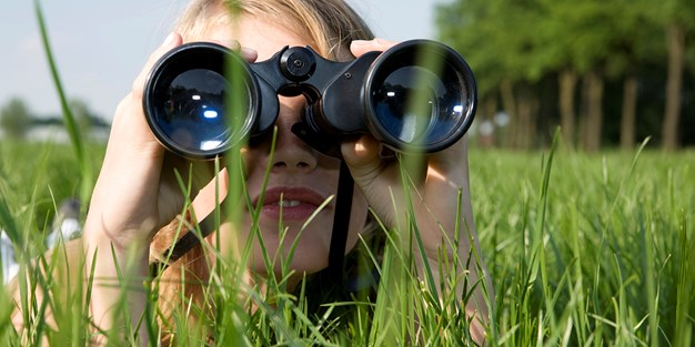A person watching with binoculars . Photo