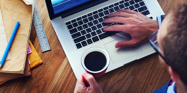 A man with one hand on the keyboard of his computer and a cup of coffee in the other hand. Photo