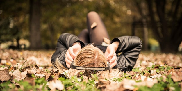 A young woman with headphones lying on her back in a park in the fall. Photo