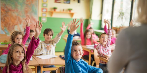 School children raising their hands ready to answer the question. Photo