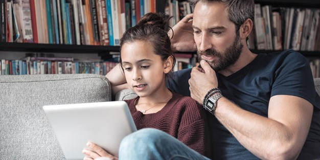 Daughter and father use a tablet. Photo
