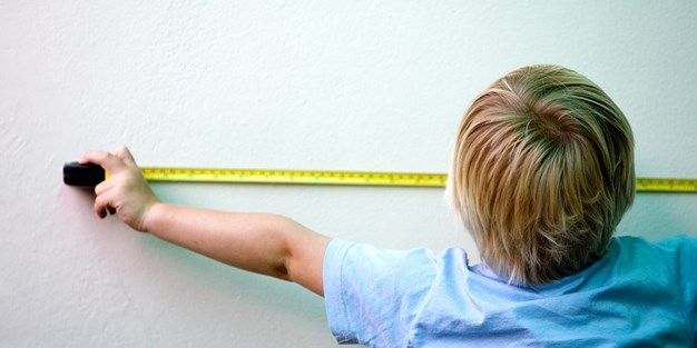A boy using a tape measure. Photo