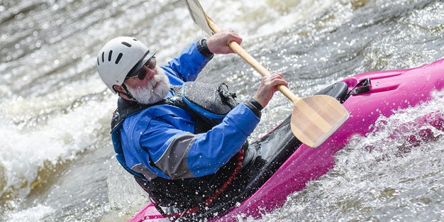 An older man kayaking in a rapid. Photograph