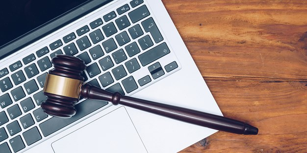 A judge hammer lying on a laptop. Photo