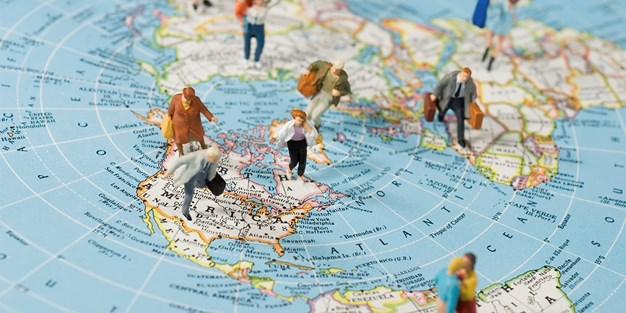 A world map with small figures placed in different countries. Photograph