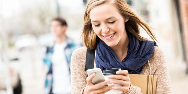 Young woman holding her mobile phone and laughing . Photo