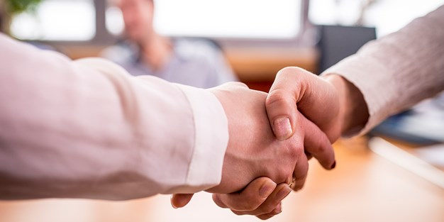 Two people shaking hands with each other. Photo