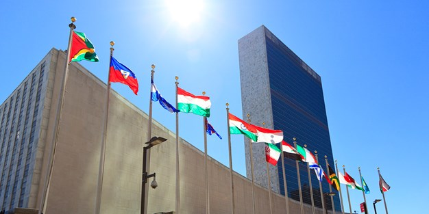United Nations Headquarters with waving flags in New York, USA. Photo