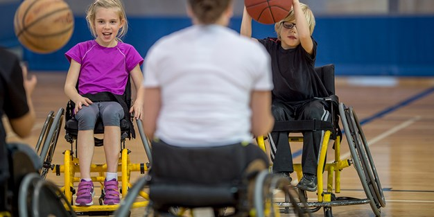 Children play basket ball in wheelchairs. Photo
