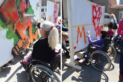 Participants in wheelchair paint graffiti with spray paint on a temporary wall. Photo Cesar Verdug Sanchez