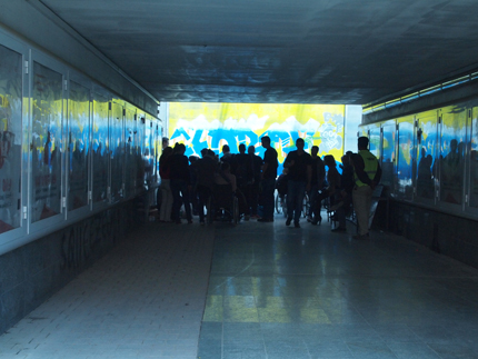 A pedestrian tunnel under the railway, in one end of it, there is a crowd of people watching when the graffiti painting is created. Photo: Cesar Verdugo Sanchez