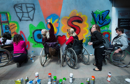 Several participants paint graffiti on a tunnel wall. Photo: Charlotta Boucht