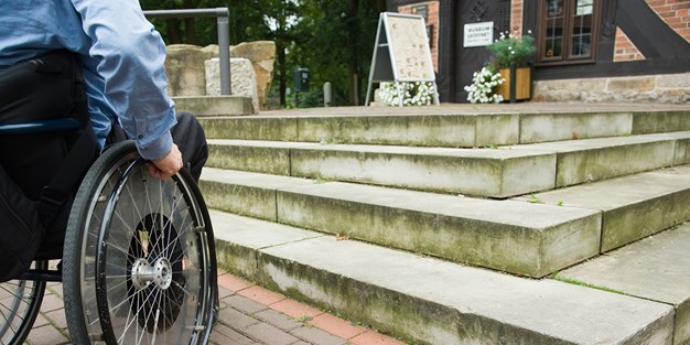 A wheelchair user in front of some stairs. Photo