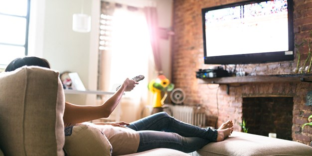 A person watching tv and using a remote control. Photo