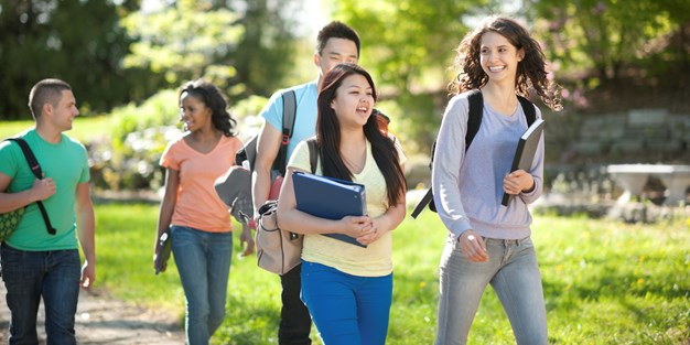 A few young students walking on a sidewalk. Photo