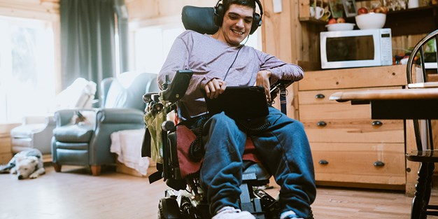 A person in a wheelchair using a tablet. Photo
