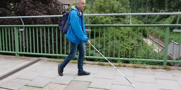 A blind person walk with a white cane. Photo
